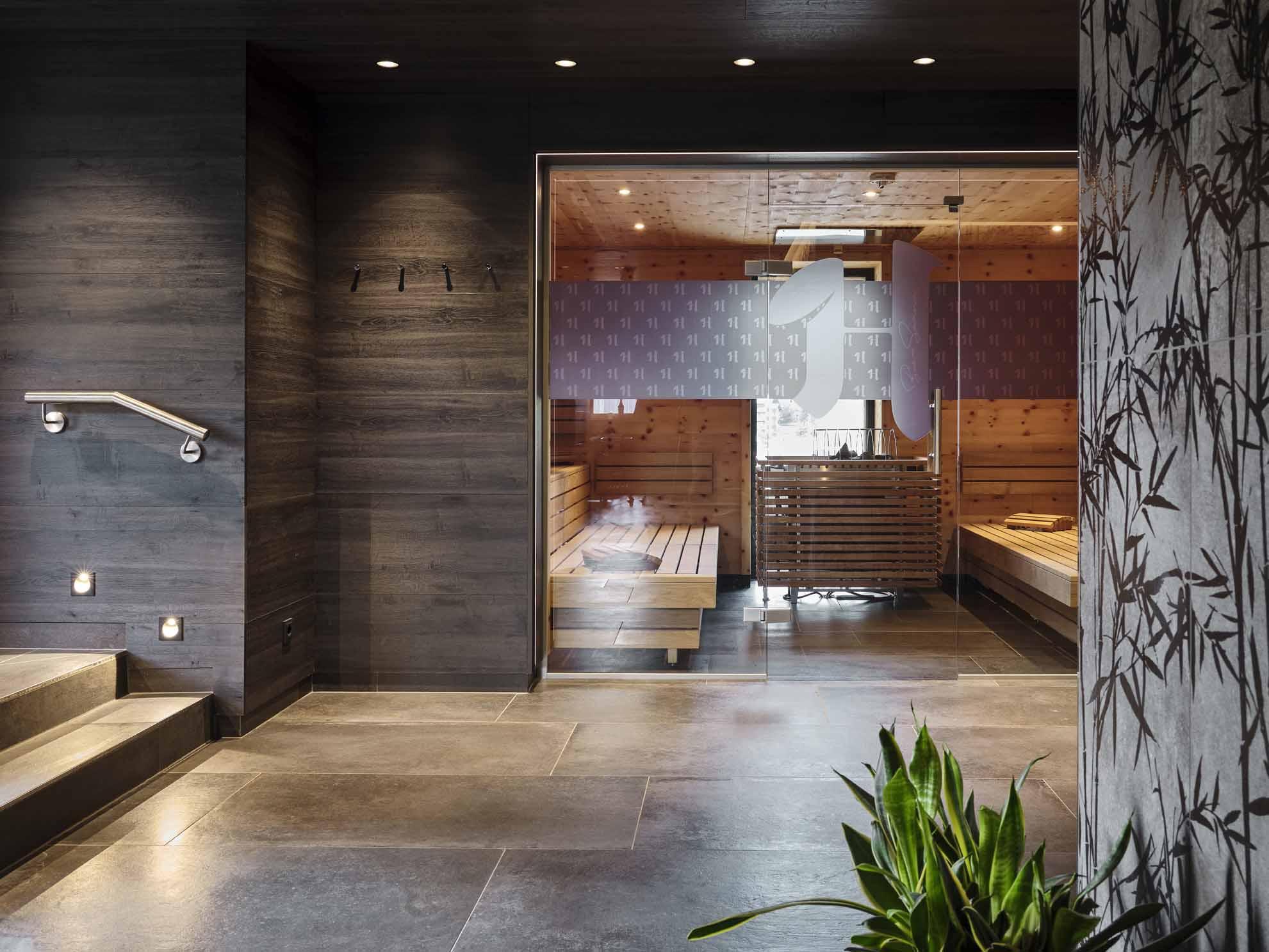Die Sauna mit einer Glastüre und dem Hasenauer-Logo im Wellness-Bereich