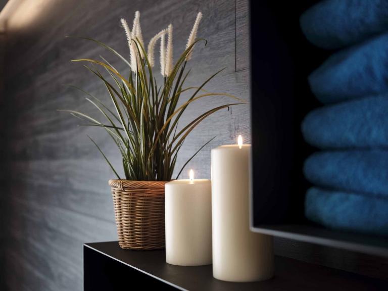 Zwei Kerzen und ein grünes Gewächs stehen auf einer schwarzen Stelage