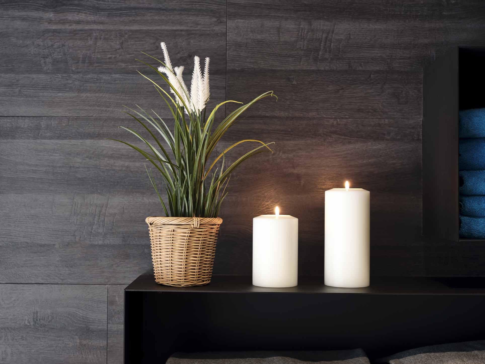 Zwei Kerzen und eine Dekorations-Blume auf einem schwarzen Untergrund