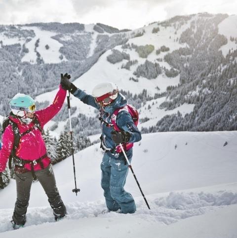 Drei Skifahrer stehen auf der Piste und zwei klatschen sich gegenseitig ein