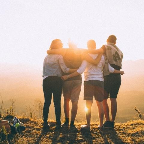 Vier Menschen stehen auf einer Wiese und haben die Sonne im Hintergrund